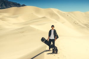 man standing with a snowboard on sand dunes
