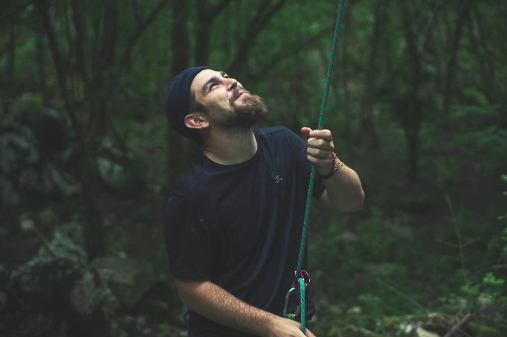 man belaying for rock climbing