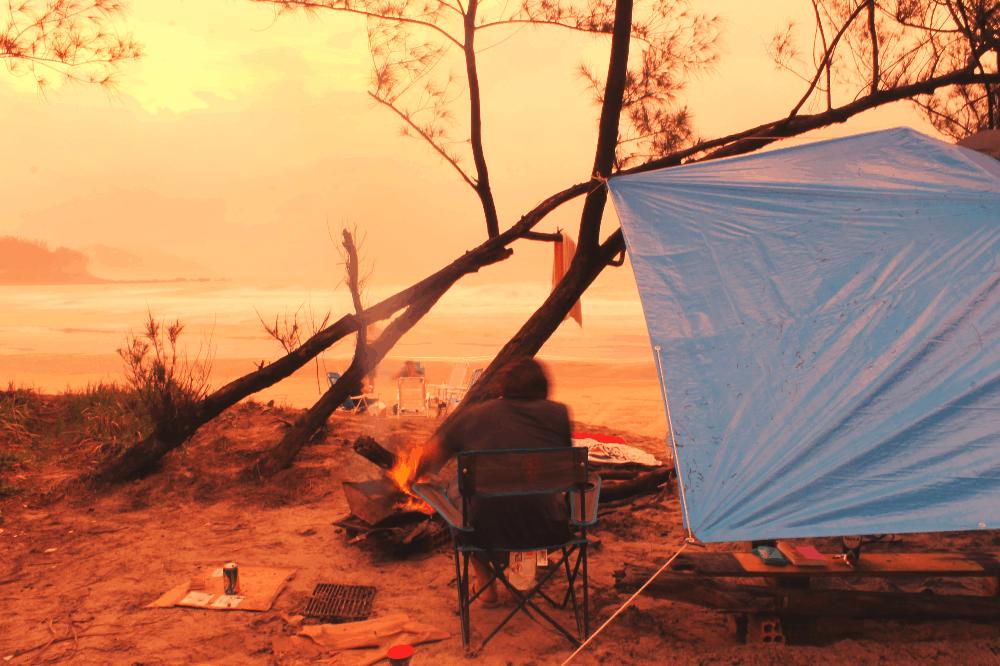 man sitting on beach next to tarp