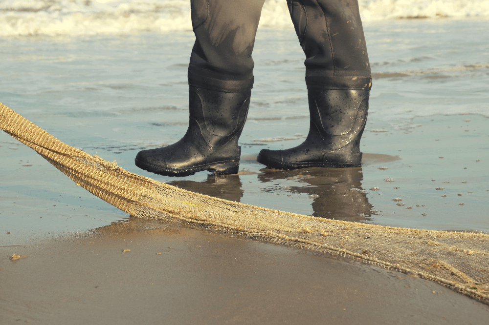 person wearing boots in the ocean