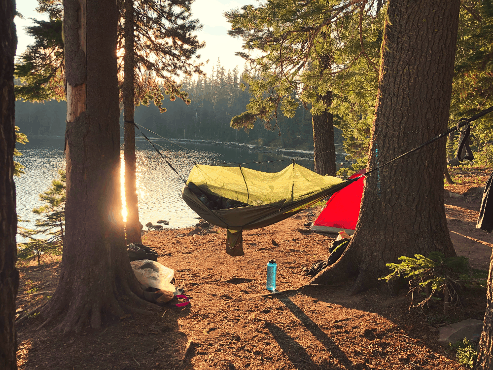 person lying in a hammock with tarp by the lake