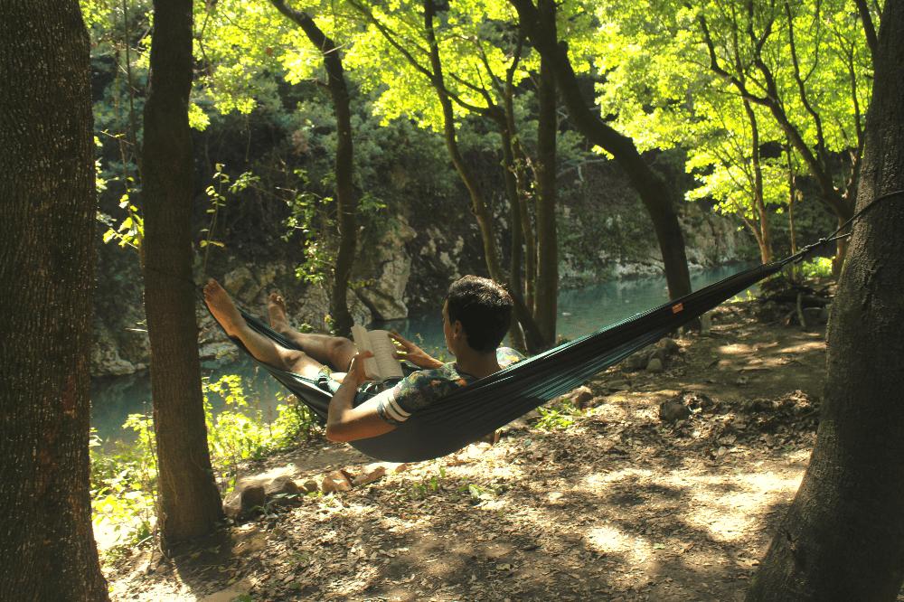 man in a hammock reading a book