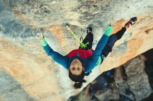 woman rock climbing on a big wall outside