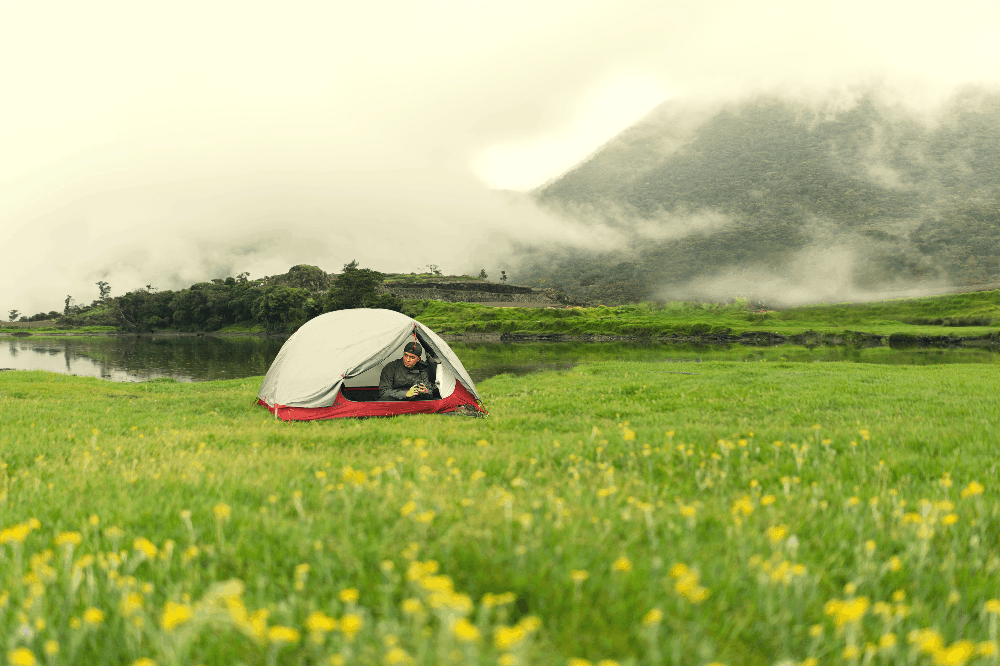 man sitting in a tent in a field next to water and mountains
