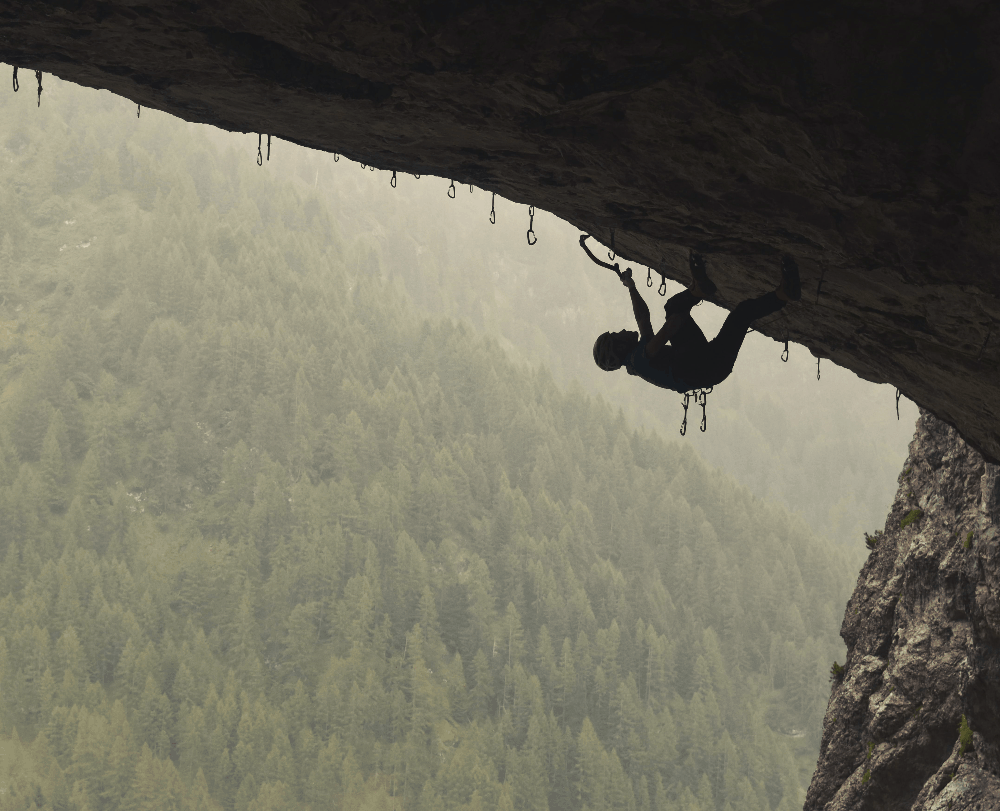 man climbing upside down in a cave