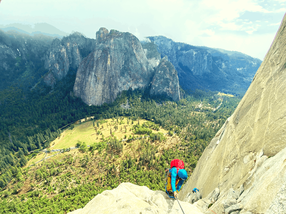two rock climbers climbing up a big wall in yosemite national park