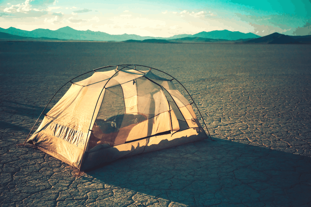 tent pitched on cracked desert land