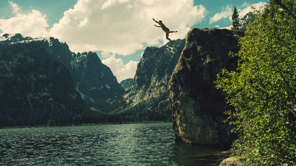 cliff jumping off a rock in wyoming grand tetons