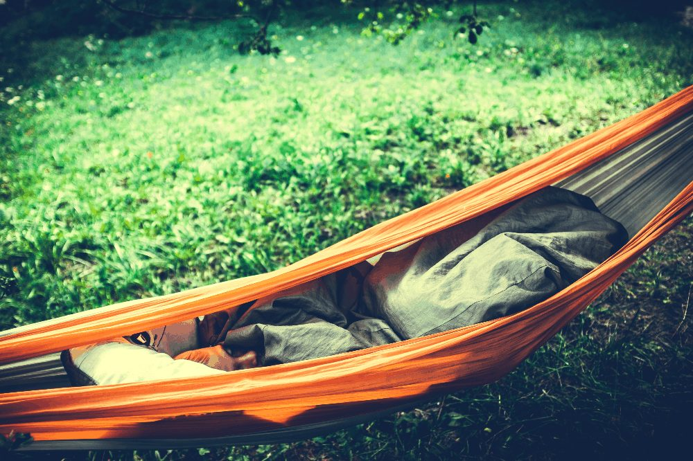 woman in a hammock with a sleeping pad and blanket