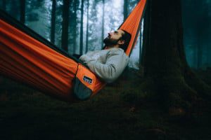 man lying in a hammock in the forest dark and moody