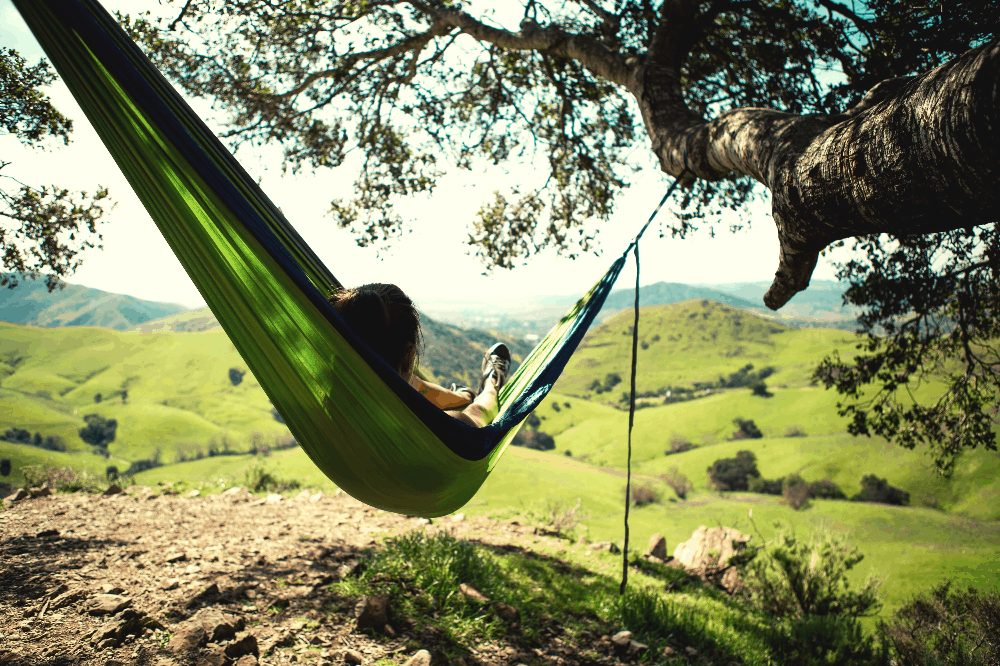 person lying in a green hammock between two tree branches with rolling hills in front of them