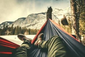man laying in a hammock in the winter