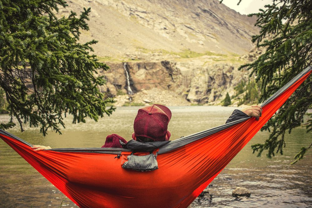 man laying in a hammock in front of a waterfall