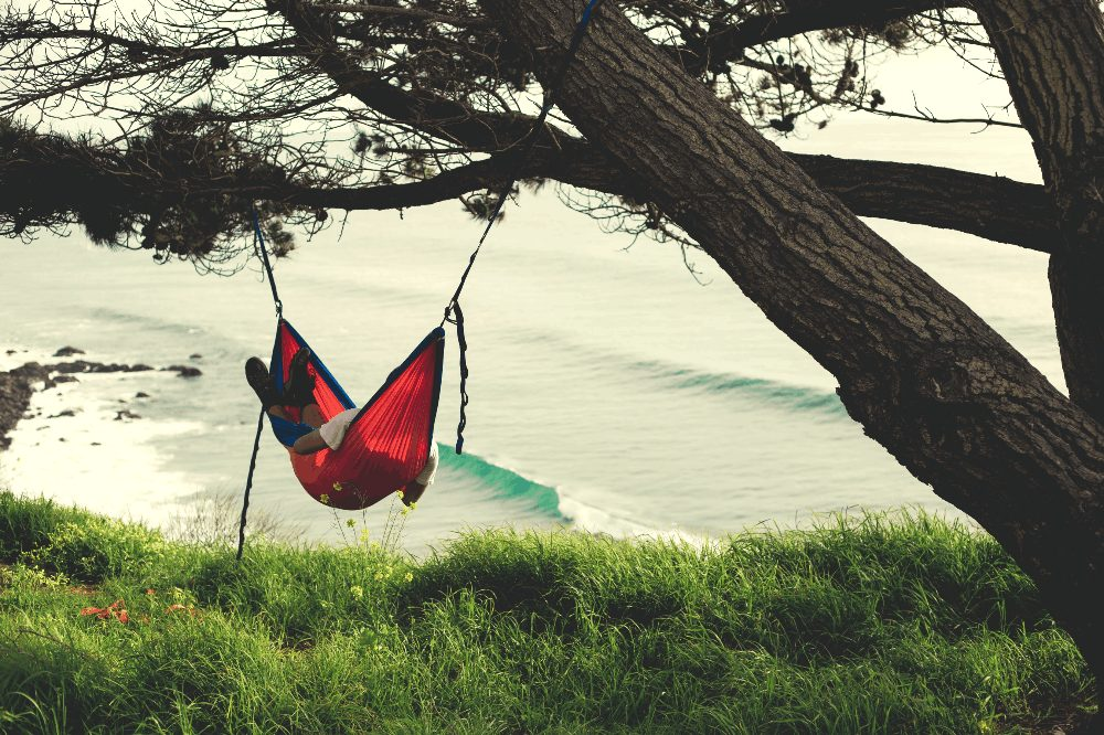 man in a hammock next to the ocean