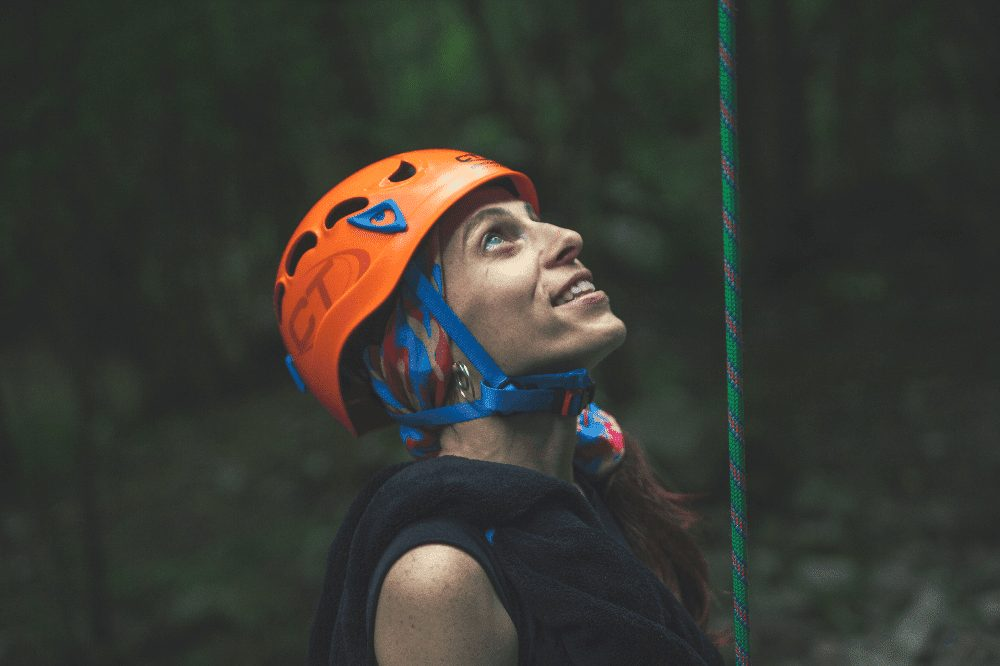 woman with a rock climbing helmet on while belaying