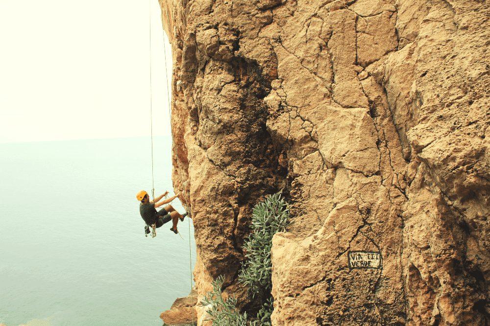 man rappelling down a rock wall
