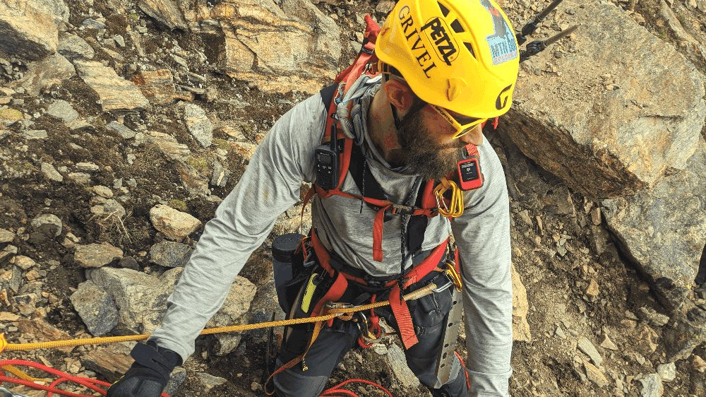 man in a yellow helmet tied into a rope while rock climbing