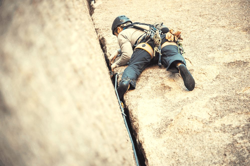 man crack climbing with a rope and trad gear on his harness