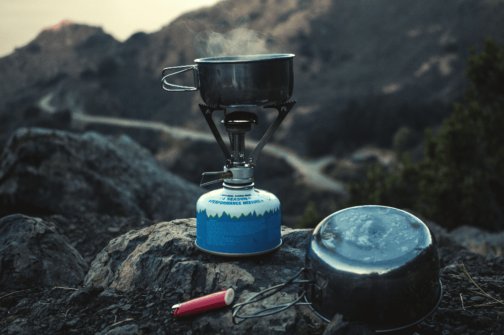 single propane stove burner for camping with a pot of boiling water