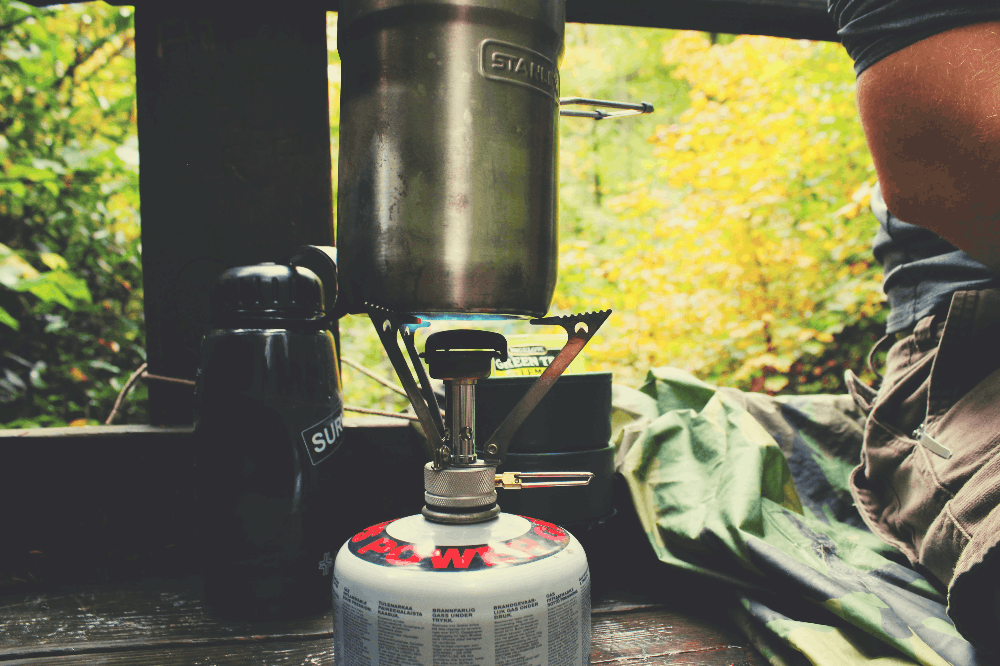 single burner propane camp stove in a shelter next to a bed