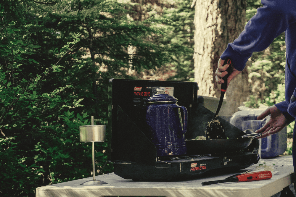 person cooking on a camp stove out in a forest