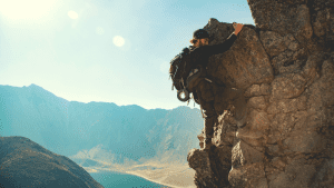 man rock climbing with his gear on his back