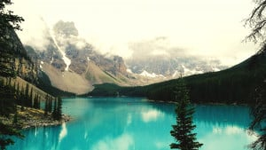 clear blue lake surrounded by pine trees with mountains in the background